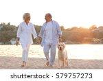 Stock photo senior couple and big dog on riverside 579757273