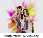 Small photo of indian couple busy on smartphone on Holi festival, with face painted with colours, and colour splash all over