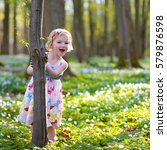 Small photo of Beautiful little girl enjoying nature on a sunny day. Adorable child playing and hiking in the forest, covered with wild white anemones, early-spring flowers.