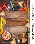 Small photo of Ozney Haman cookies and other Purim items framing a wooden background