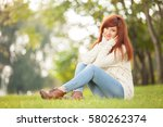 young woman walking in the park.... | Shutterstock . vector #580262374