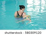mother with baby in swimming... | Shutterstock . vector #580309120