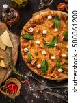 pizza on the black table | Shutterstock . vector #580361200