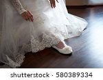 bride putting on wedding shoes | Shutterstock . vector #580389334
