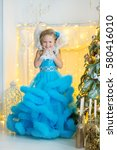 Small photo of Cute beautiful young girl in airy fairy blue dress with stylish blond curly hair close to Christmas New Year tree with marvel uncommon toys smiling and celebrating holidays with snow man.