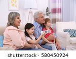 happy family watching tv on... | Shutterstock . vector #580450924