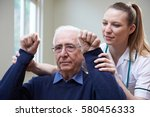 Stock photo nurse assessing stroke victim by raising arms 580456333