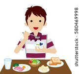 young man eating breakfast | Shutterstock .eps vector #580469998