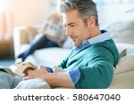 couple at home reading book ... | Shutterstock . vector #580647040