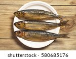 Stock photo smoked herring in white plate on old wooden table top view 580685176