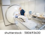 radiologist putting coil on... | Shutterstock . vector #580693630