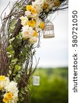 Small photo of Decorative white bird cages hang on osier wedding altar