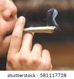 man smoking joint  cigarette ... | Shutterstock . vector #581117728