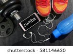 Small photo of Fitness, healthy and active lifestyles concept. Dumbbells, sport shoes, smart phone with earphone and water bottle gym floor with word zumba