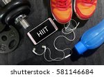 Small photo of Fitness, healthy and active lifestyles concept. Dumbbells, sport shoes, smart phone with earphone and water bottle gym floor with word hiit