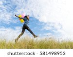 happy woman jumping on green... | Shutterstock . vector #581498953