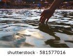 human hand touching sea water. | Shutterstock . vector #581577016