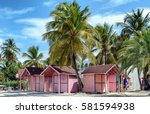 Pink Huts Among Palm Trees In...