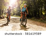 Two mountain bikers riding bike in the forest on dirt road. - stock photo