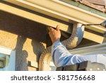 worker attaching aluminum rain... | Shutterstock . vector #581756668