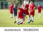 boys kicking football on the... | Shutterstock . vector #581883340