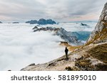 Person standing and enjoying the view from Mangart mountainst, located between Italy and Slovenia. In the background with foggy peaks of Triglav - stock photo