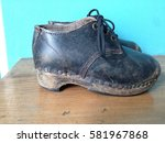 Small photo of Vintage British children's clogs, leather lace up with wooden soles and clog irons, side and under sole view, foot wear