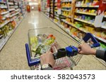shopper pushes a cart with... | Shutterstock . vector #582043573