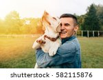 Happy Young Man Holding Dog...