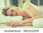 pretty woman lying down on her... | Shutterstock . vector #582122290