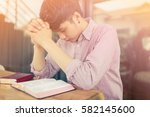 man praying on holy bible in... | Shutterstock . vector #582145600