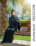 Small photo of Confident Arab woman and laptop. Arab businesswoman wearing hijab working on a laptop in the park on the background of skyscrapers of Dubai. The woman is dressed in a black abaya