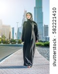Small photo of Confident businessman sweeping the Arab Dubai. Arab Business vumen hijab is in the streets against the skyscrapers of Dubai. The woman is dressed in a black abaya