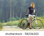 Young Woman On Bike Standing O...
