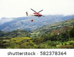 Small photo of Taiwan February 16, 2017: Rescue helicopters carrying water to perform fire fighting mission in the mountain area which is subordinate to National Airborne Service Corps,Ministry of Interior, Taiwan