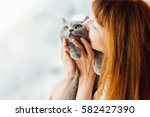Stock photo close up of lovely middle aged redhead woman kissing gray cat 582427390