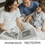 Small photo of Family Looking Photobook Together at the Bedroom