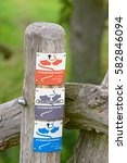 Small photo of APELDOORN, THE NETHERLANDS, AUGUST 3, 2016 - Direction signs are affixed on a pole marking the hiking trails in rural areas in Gelderland. These trails are called Klompenpaden - Wooden clogs trails.