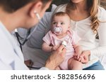 beautiful young mom is holding... | Shutterstock . vector #582856696