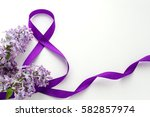 Small photo of International Women's Day. 8 March. Decoration with Purple Ribbon and Lilac on a white background. Greeting Card.