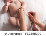 young mom is changing her cute... | Shutterstock . vector #582858370
