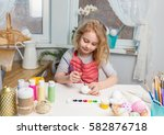 little blonde girl coloring... | Shutterstock . vector #582876718