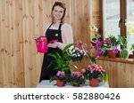 happy young woman watering... | Shutterstock . vector #582880426