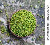 Small photo of Mung bean, green moong dal in wooden bowl. Copy space. Grey background.
