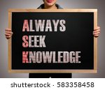 Small photo of Girl (manager, student, businesswoman) in casual clothes holding a black chalk board with the text Always seek knowledge (ASK)