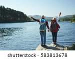 Small photo of Adventurous seniors waving hands in front of lake