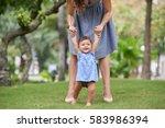 mother helping her baby...   Shutterstock . vector #583986394