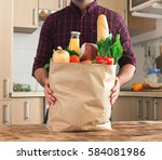 Small photo of Man holding a paper bag full of healthy food on a wooden table in the home kitchen