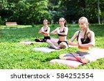 women practicing yoga in the... | Shutterstock . vector #584252554
