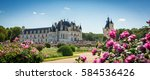 Scenic panoramic view of Chateau de Chenonceau looking across the formal gardens with pink roses in bloom in summer situated in the Loire Valley spanning the river Cher